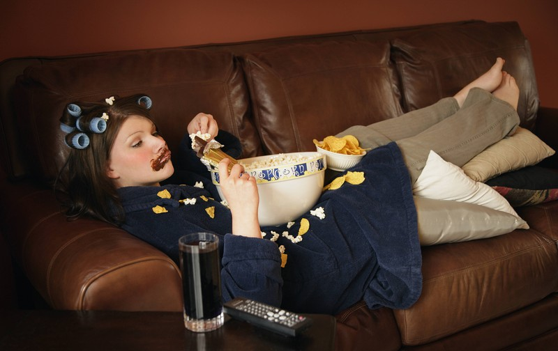 Frau sitzt vor dem Fernseher und schaut Netflix und probiert die neue Funktion aus, Filme in erhöhter Wiedergabegeschwindigkeit abspielen zu lassen