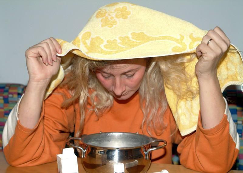 Eine Frau inhaltiert mit einem Dampfbad, das gegen Schnupfen hilft