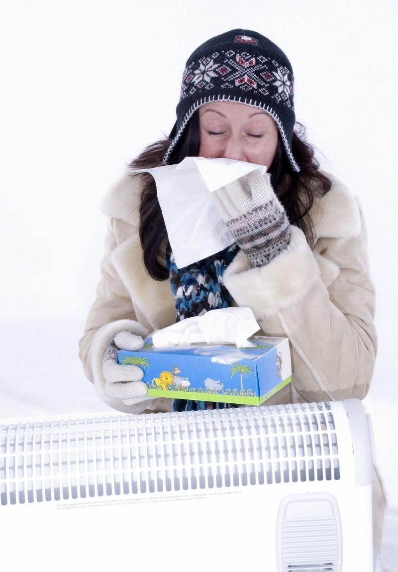 Eine Frau ist krank, hat eine verstopfte Nase und wärmt sich an der Heizung