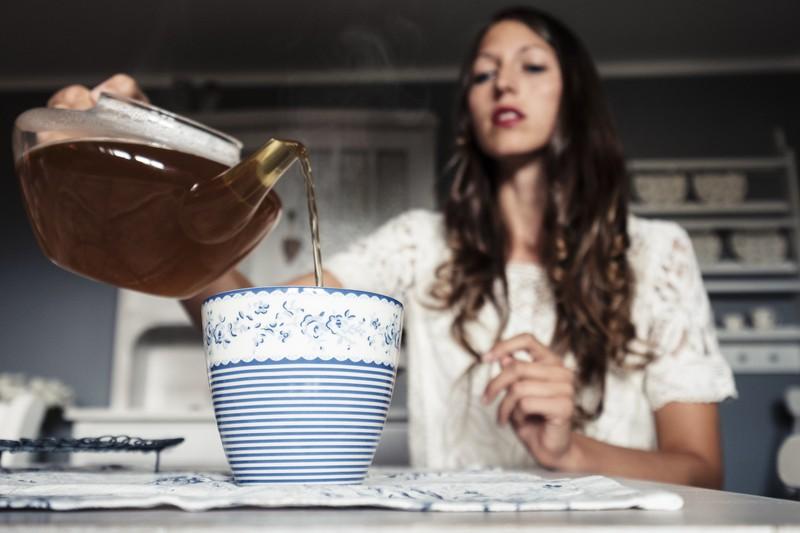 Eine Frau kocht heißen Tee auf und gießt ihn in eine Tasse