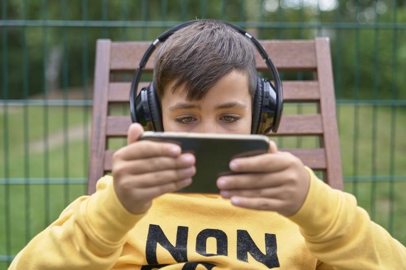 Ein  Kind spielt mit seinem Smartphone und schaut ein Video