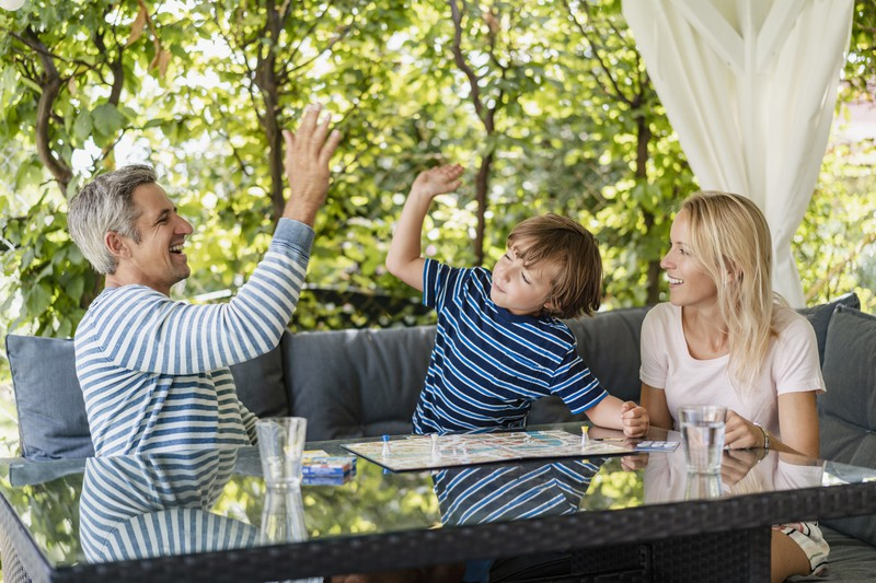 Man erkennt einen Vater, der sein Kind unterstützt und ein High Five gibt