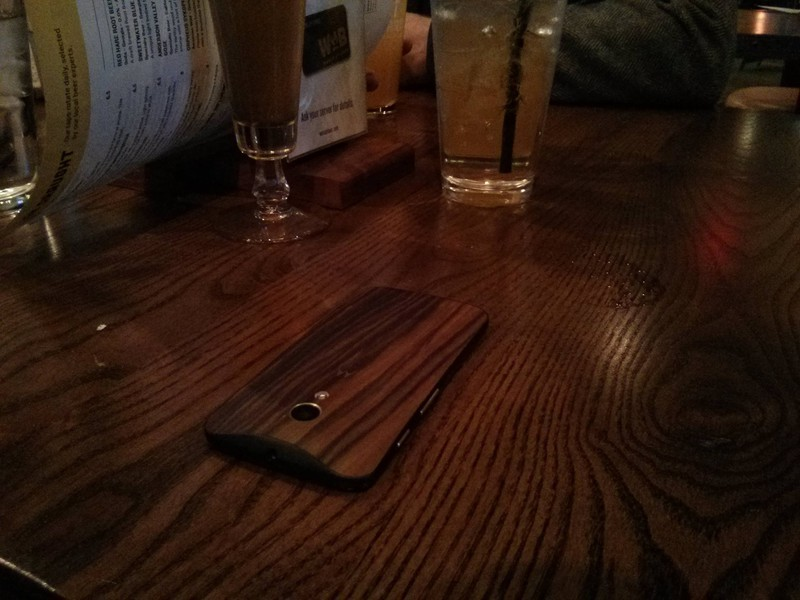 Man sieht ein Handy, dass der Vater verloren hat, weil die Handyhülle nicht vom Tisch zu unterscheiden ist