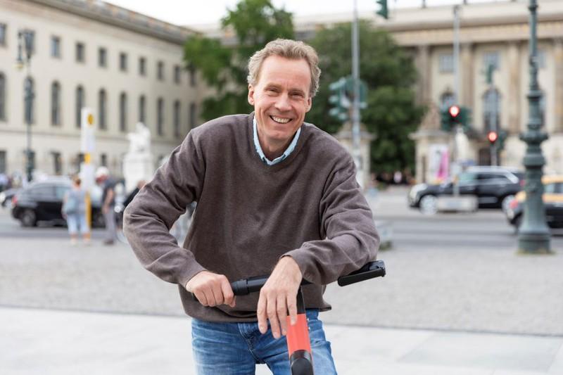 Man sieht einen Mann, der mit dem E-Scooter fährt
