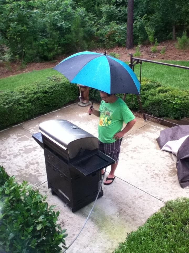 Man sieht einen Vater, der im Regen steht und trotzdem grillt