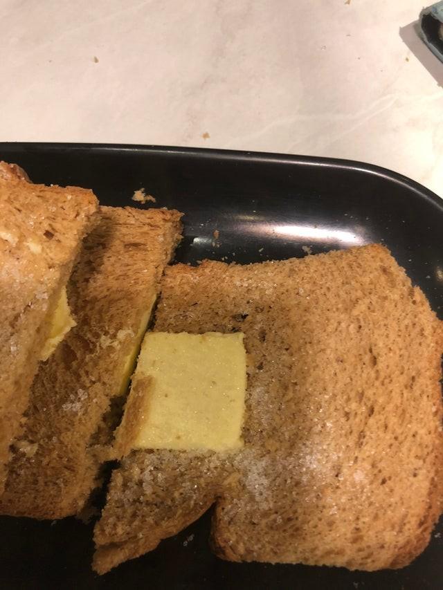 Das Foto zeigt ein Toastbrot mit Butter und Zucker.