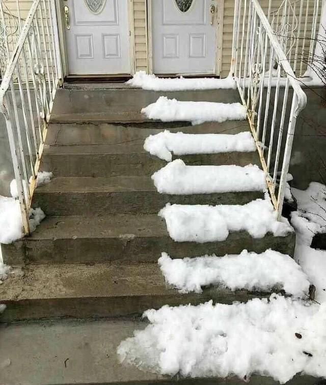 Man sieht eine Treppe vor einem Haus, wo ein Nachbar nur die eine Hälfte den Schnee geschaufelt hat