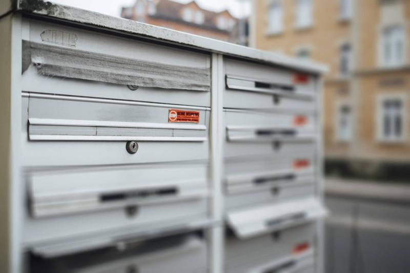 Man sieht einen Briefkasten mit mehreren Fächern, also mehrere Nachbarn