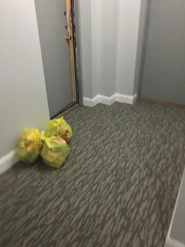 Man sieht einen Hausflur, in dem Müllsäcke liegen