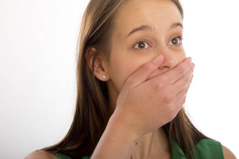 Das Mädchen auf dem Foto hält sich peinlich berührt die Hand vor den Mund.