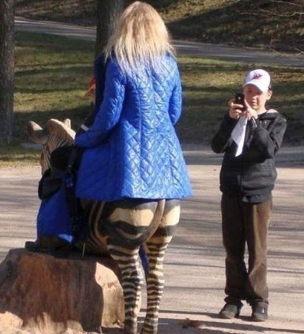 Ein Junge macht ein Foto einer Frau, bei der es aussieht, als hätte sie einen Zebra-Hintern.