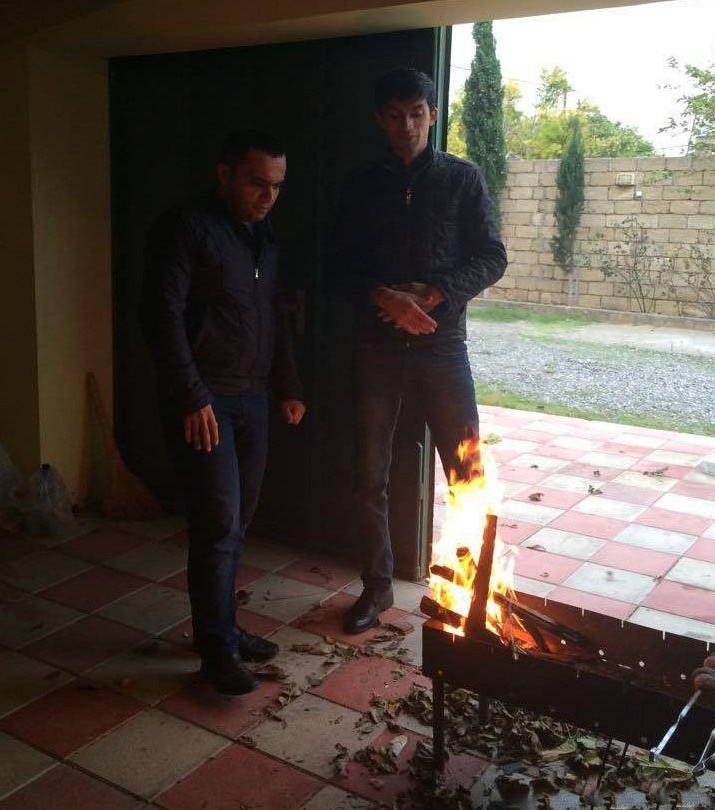 Zwei Männer stehen vor einem Feuer und es wirkt so, als würde das Bein eines Mannes brennen.