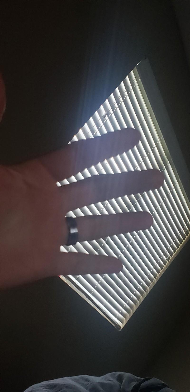 Finger, die gezackt aussehen, wenn man sie vor die Jalousie hält
