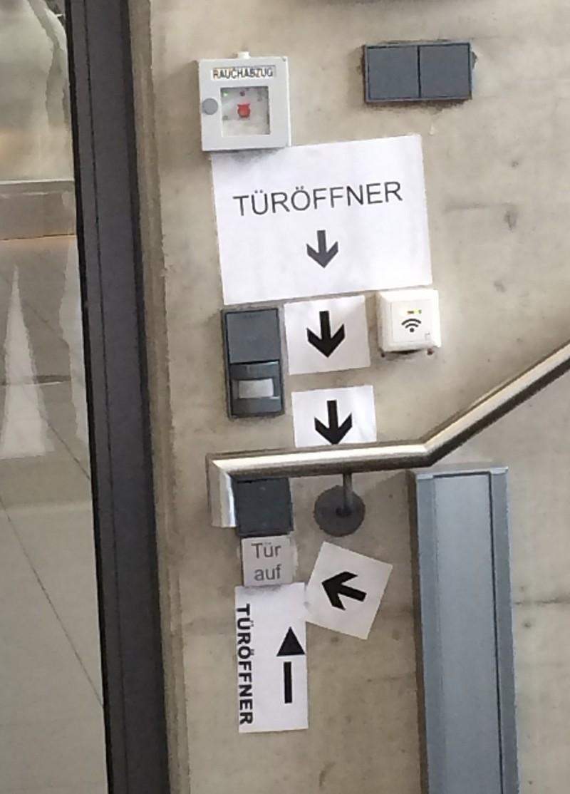 Ein Foto mit mehreren Schildern, der den Türöffner zeigt und auf ihn hinweist