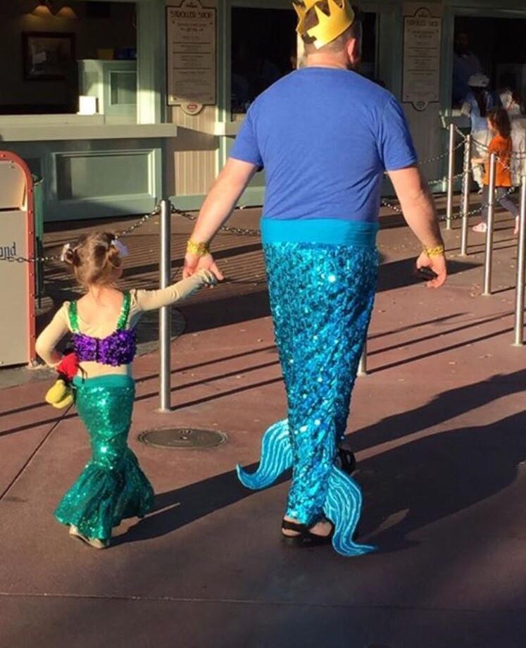 Der Vater macht die lustige Verkleidung der Tochter mit.