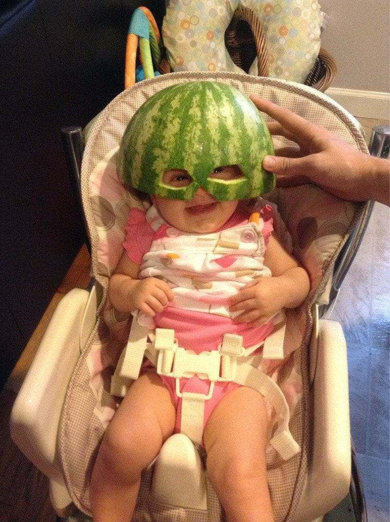 Ein Baby mit einer Maske aus einer Melonenschale