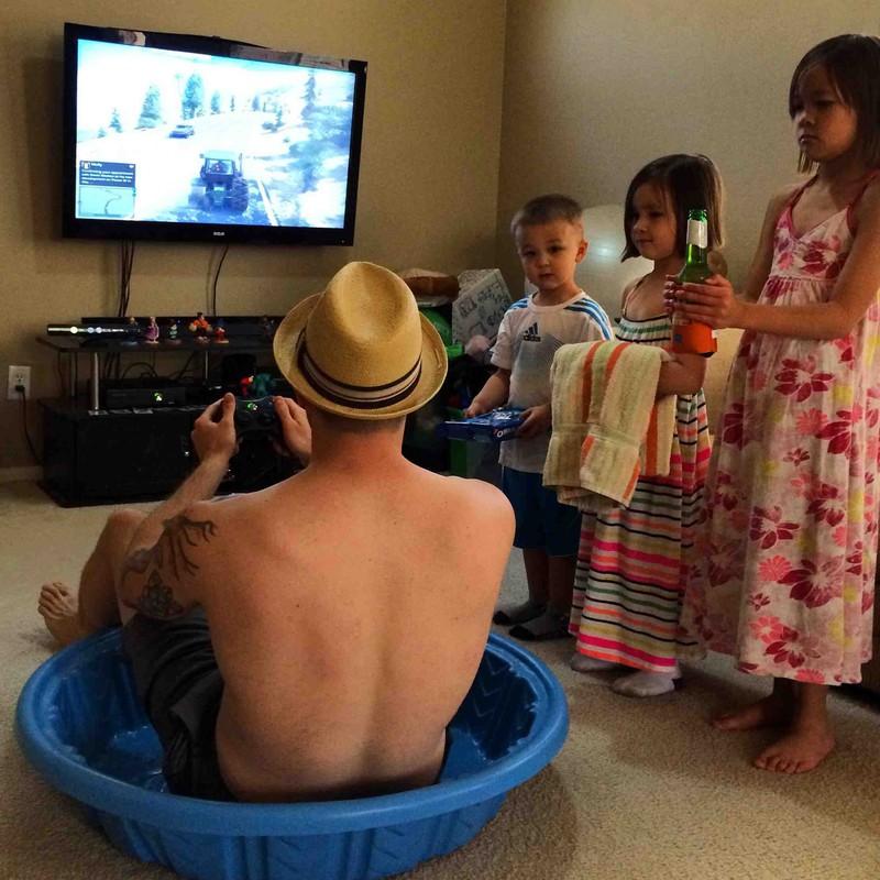 Vater lässt sich von seinen Kindern bedienen