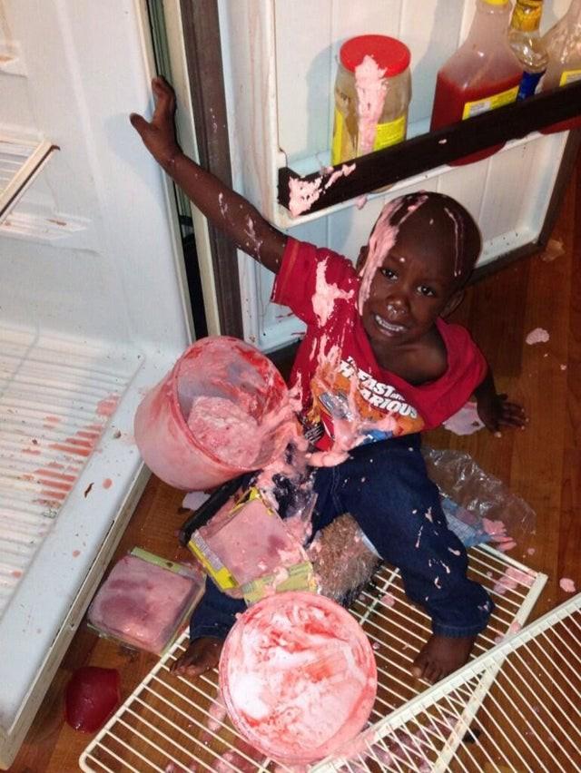 Junge, der sich Eis aus dem Kühlschrank klauen wollte