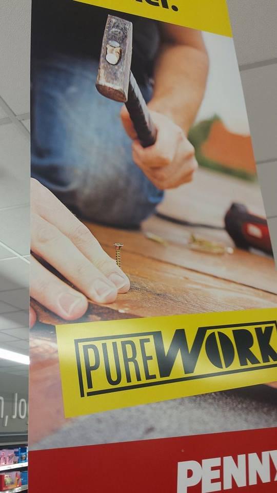 Ein Mann versucht auf dem Plakat eine Schraube zu hämmern.