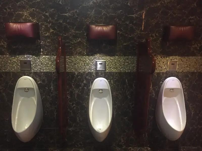 Das Foto illustriert Urinale, die oben drüber eine Kopfstütze haben, was für Männer total genial ist, wenn sie zu viele Drinks hatten