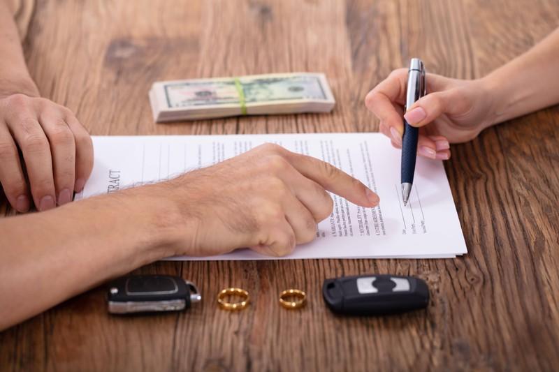 Zwei Menschen, die beim Scheidungsanwalt gerade ihre Scheidung unterschreiben