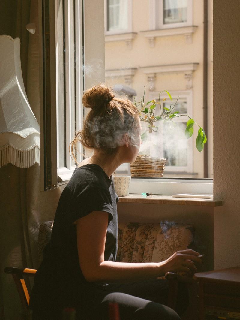 Ein Foto einer Frau die am Fenster in der Wohnung raucht und aufgrund des Wlan Routers aufgeflogen ist