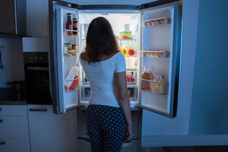 Es ist eine Frau  zu sehen, die im Kühlschrank vielleicht Croutons einfriert, damit sie als Snack essbar sind.