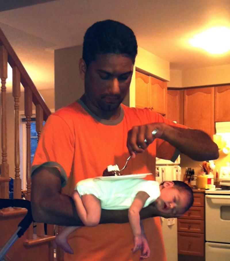 Ein Vater, der sein Baby als Tablet benutzt