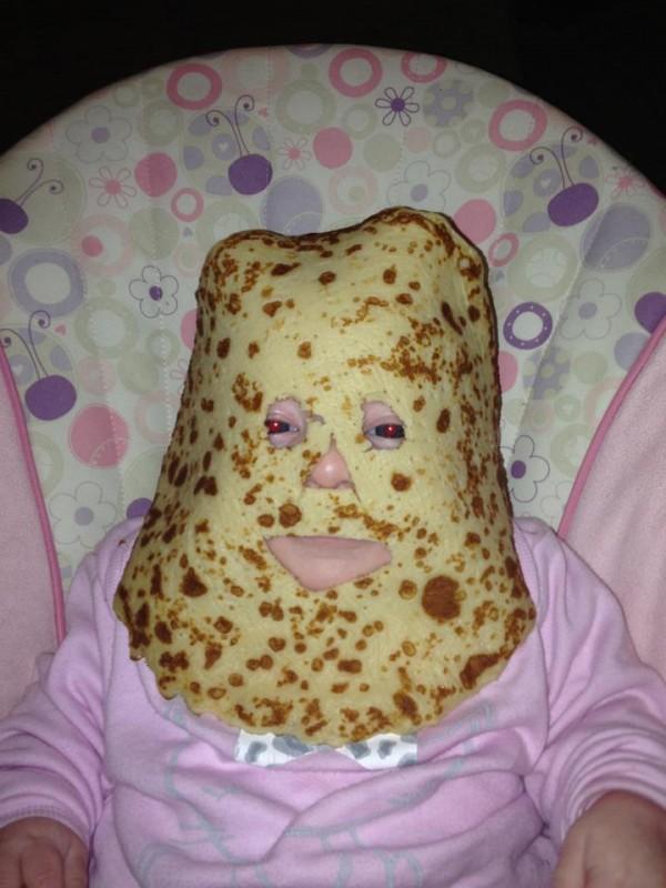 Ein Vater, der seinem Kind einen Pfannkuchen auf das Gesicht gelegt hat