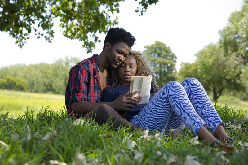 Ein Paar sitzt verliebt im Park und liest ein Buch