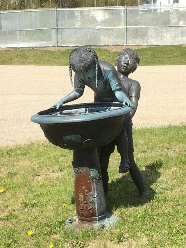 Ein Brunnen-Design, dass sehr merkwürdig aussieht, dadurch dass der Junge das Mädchen von hinten anhebt.