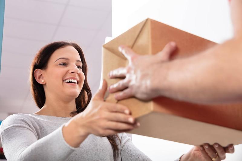 Frauen freuen sich oftmals besonders über ihre Pakete, die sie online bestellt haben.