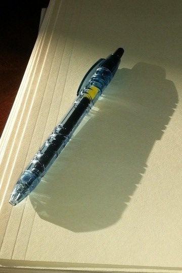 Der Schatten sieht aus wie die Wasserflasche, aus dem der Stift gemacht wurde.