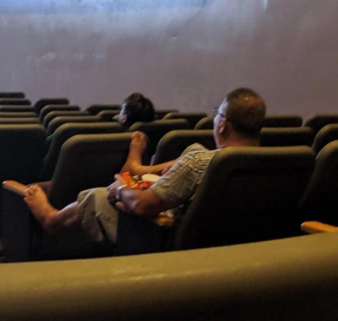 Ein Mann legt seine nackten Füße auf die Kinositze