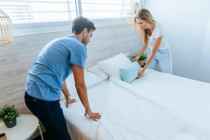 Das Paar bezieht die Bettwäsche ihres Betts neu.