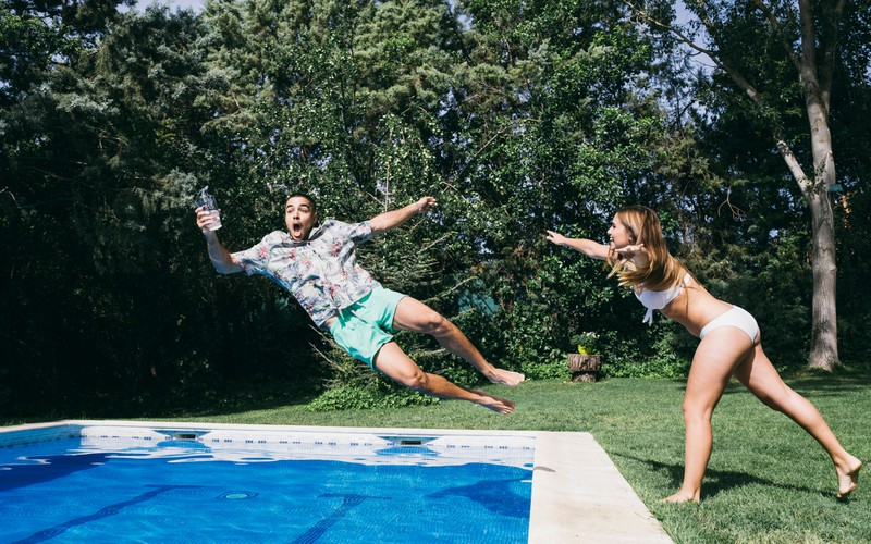 Eine Frau schmeißt einen Mann in den Pool, weil es im Sommer in Deutschland schön warm werden soll