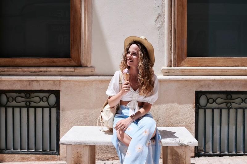 Eine Frau sitzt mit einem Eis auf einer Bank und genießt den Sommer 2020.