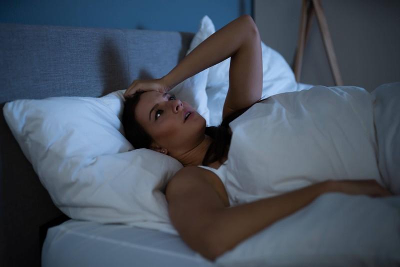 Die Frau leidet in der Nacht unter der Hitze in ihrem Schlafzimmer.