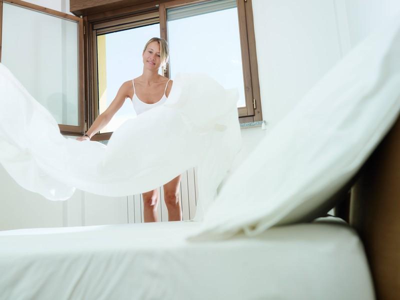 Die Frau lüftet morgens ihr Zimmer, damit ihr Zimmer abkühlt.