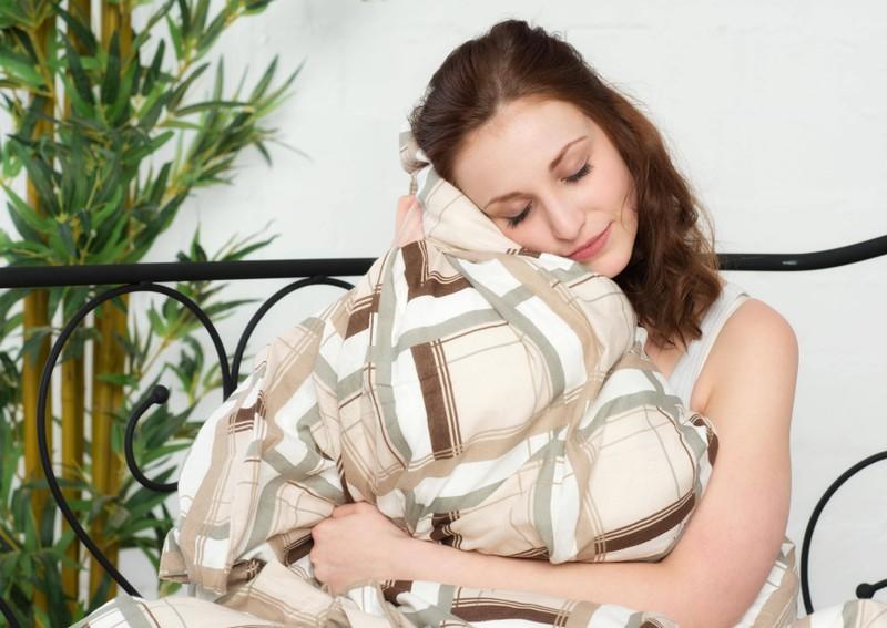 Ein Mensch, der unter einer Bettdecke liegt, die im Schlaf für Gelassenheit aufgrund des Hormons Seretonin sorgt