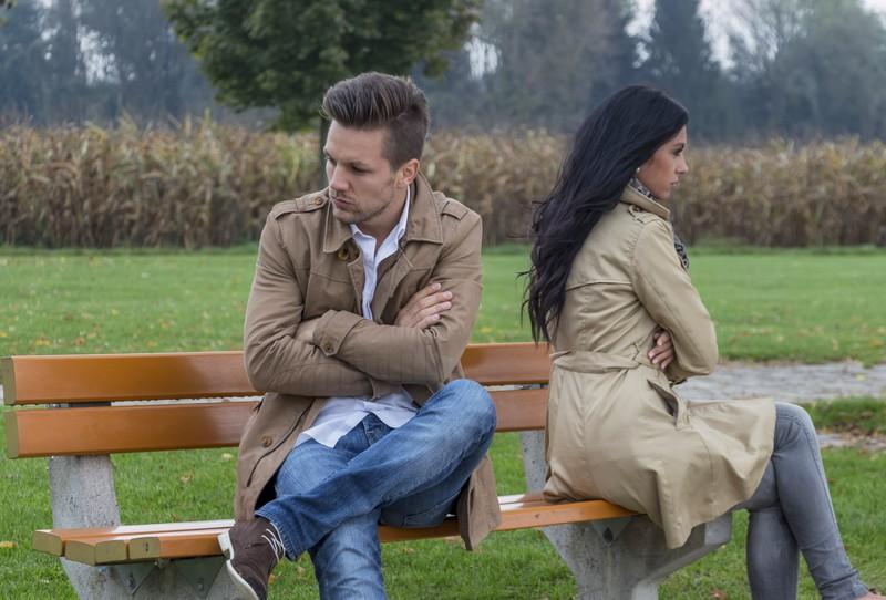 Ein Paar sitzt auf der Bank und schweigt sich an