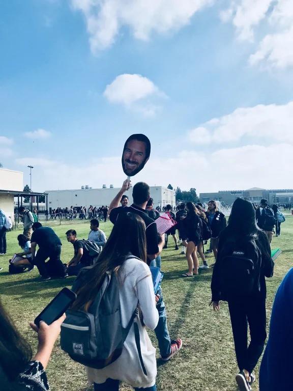 Ein Lehrer, der sein eigenes Gesicht auf Pappe ausdruckte, um die Gruppe zusammen zu halten