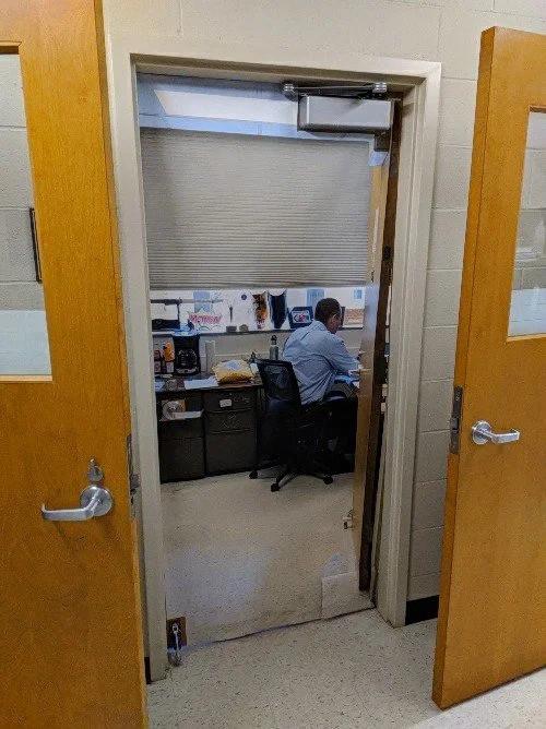 Ein Lehrer, der sich eine durchsichtige Tür einbauen hat lassen