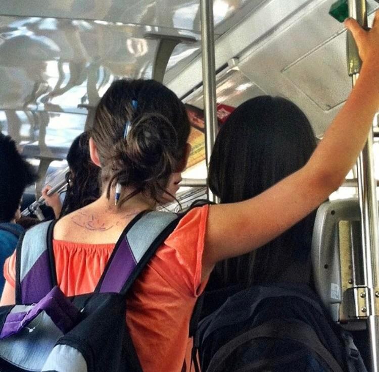 Eine Frau benutzt einen Kulli, um ihre Haare zusammenzuhalten und begeht dabei einen Fehler, den sie bedauern wird.