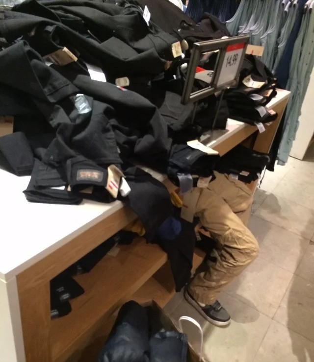 Ein Junge, der keine Lust mehr auf Shopping hat und sich unter Hosen versteckt