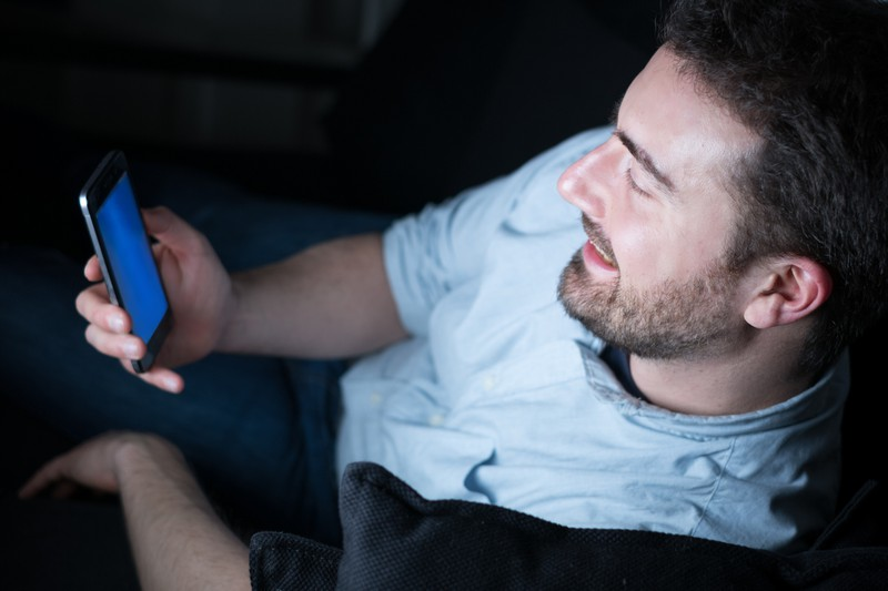 Der Mann schläft schlecht, weil er unterbewusst immer und immer wieder auf sein Handy achtet.