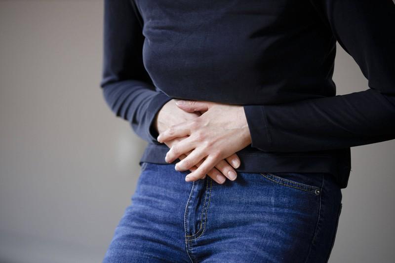 Eine Frau, die evtl. Funktionsstörungen des Beckenbodens aufweist, weil sie ihr Handy immer mit auf die Toilette nimmt
