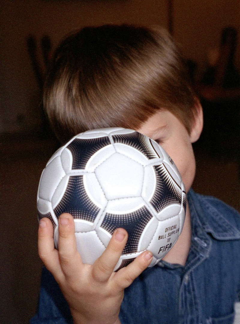 Der Junge verbarg den Ball vor seinen Eltern.
