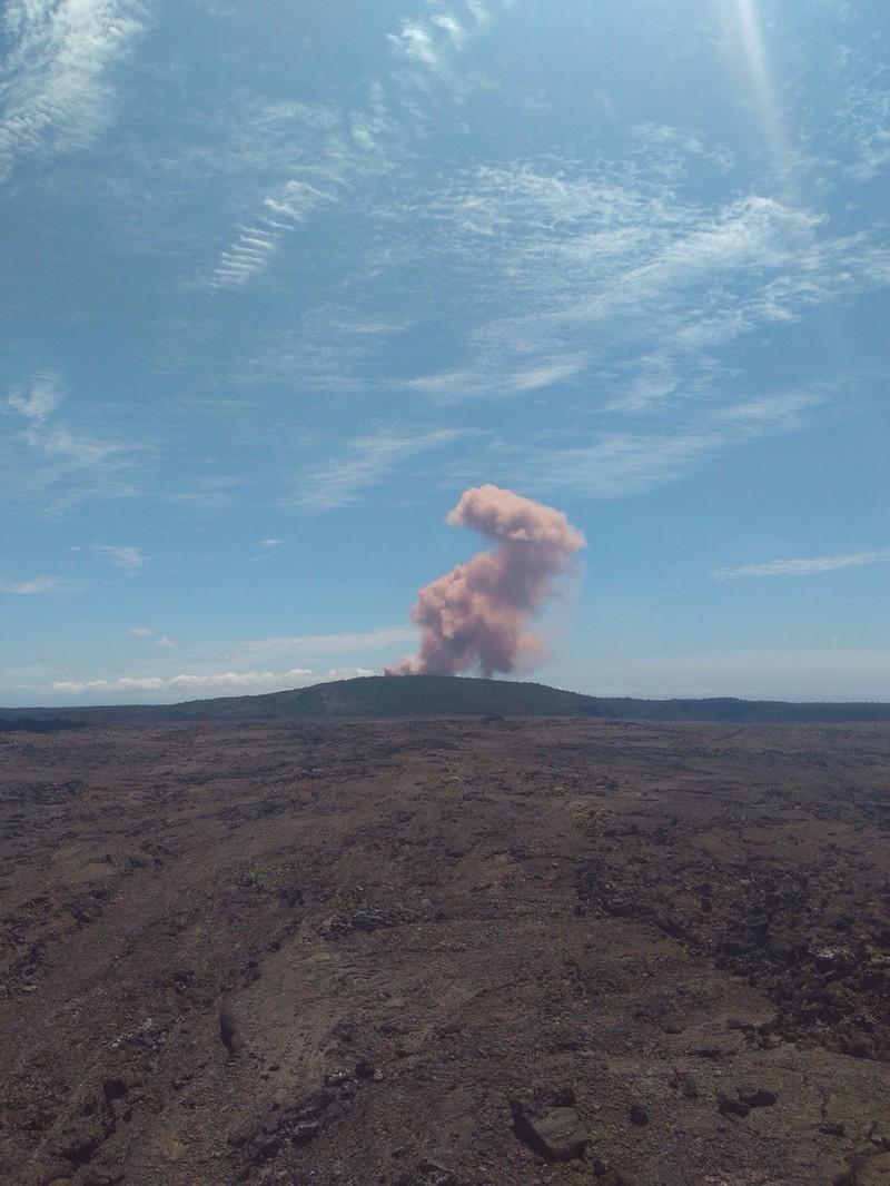 Ein Mann, der am Fuße eines Vulkans steht und fotografiert