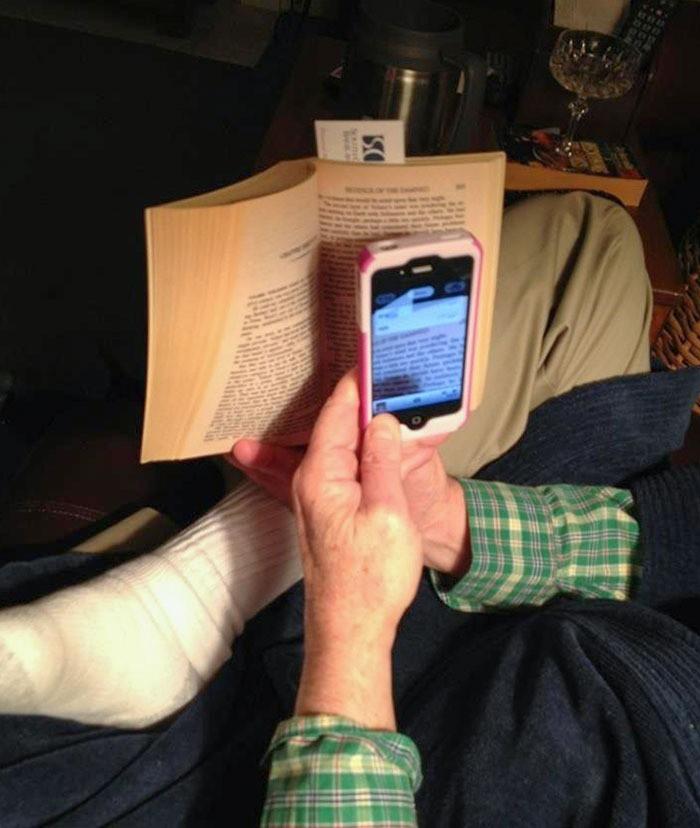 Mann liest sein Buch durch die Kamera App seines iPhones